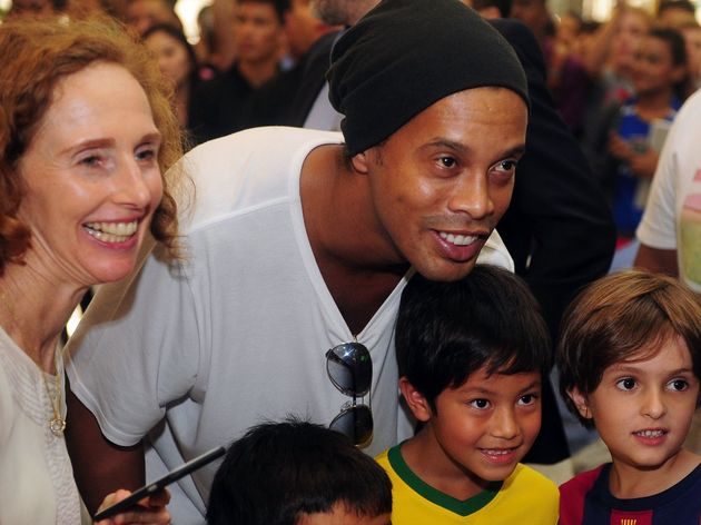 Brazil's football player Ronaldinho (C) poses during a meet and greet session with fans in Singapore on December 10, 2015. Brazilian legend Ronaldinho on December 10 signed an agreement to establish a football academy in soccer-mad Singapore, the local club that he partnered with said. AFP PHOTO / MOHD FYROL / AFP / MOHD FYROL (Photo credit should read MOHD FYROL/AFP/Getty Images)